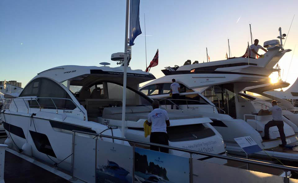 CleanToGleam workers washing luxury motor yachts at boat show